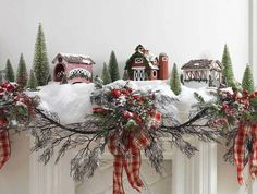 Mantel with snow blanket, houses, trees, and garland