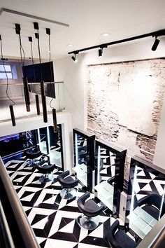 The decor of this modern elegant beauty salon creates a sense of luxury through the use of black and white tile patterns.  The interior design is sophisticated with its use of bronze sheer curtains to create private treatment rooms. Other decor ideas are the use of sleek styling stations giving a boutique hair salon ambience. | #rustic | #hair | #lighting |
