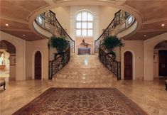 Mediterranean Staircase with complex marble floors, Arched window, Custom wrought iron stair railing, Double staircase