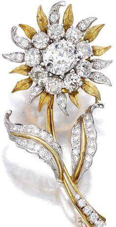 A diamond flower brooch designed as a textured gold sunflower, centering an old mine-cut diamond, weighing 2.65 carats, within an old-cut diamond surround, enhanced by circular-cut diamond detail; estimated remaining diamond weight: 4.05 carats; mounted in eighteen karat gold and platinum; length: 2 1/2in.