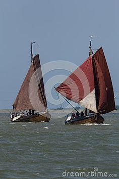 Two botters sailing over the sea. Botters are traditional Dutch sailing ships used to catch fish. The type was first used in the second half of the eighteeth century and was still in use in the 1950's when the modern trawlers appeared. There are various versions, specially built for the region where they were used.