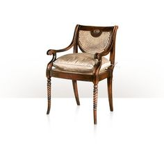A hand carved armchair, the verdigris brass oval inset and caned back above a silk tie on cushion seat, on spiral turned legs. The original Regency.