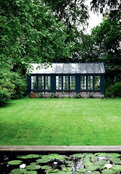 Specially designed greenhouse in petroleum blue is an eye catcher in the garden. Built from recycled windows in heartwood.
