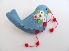 felted bird with a string of hearts