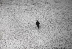 A man walks across Broadway in Times Square as snow falls in New York, January 21, 2014. REUTERS-Gary Hershorn