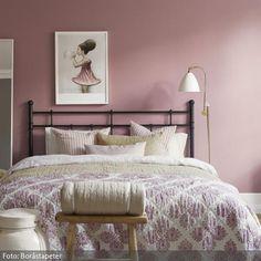 Die Wandfarbe und Bettwäsche in Rosa wirken sanft und feminin, was durch das Wandbild noch verstärkt wird. Mit einer großen Tagesdecke, die bis zum Boden reicht, macht das Bett einen noch kuscheligeren Eindruck. Zusätzlich sorgen Teppiche für Wärme.
