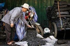 Shovelling coal, Phnom Penh (Cambodia)