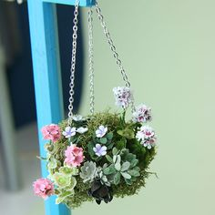 Mini Hanging Basket:  Flowers can add color to a miniature scene. These easy to make miniature hanging baskets can be made to suit any season in scales as small as 1:48. The baskets take only minutes to make, and you can vary them to create all kinds of seasonal interest. Make them with traditional paper or silk flowers in miniature, or use floral scatter for smaller scales. Winter baskets can be made with greenery, pine cones and velvet bows to match miniature Christmas wreaths.