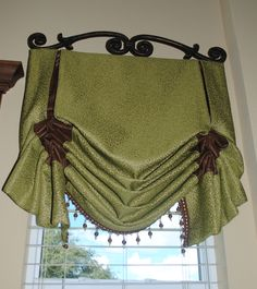 Decorative ironwork creates additional focal point - I would have spray painted the ironwork brown to coordinate with valance colors.