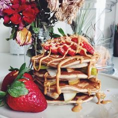 Buckwheat pancakes with layers of pears and topped with some strawberries  and peanut butter ❤️