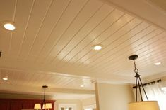 Cover up popcorn ceiling with stunning results. The ceiling is made up of individual 5 inch wide tongue and groove pine planks bought at Lumber Liquidators. The beams are box beams (hollow inside).