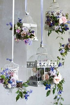 Birdcages filled with pretty blooms and hung at different levels by ribbons.