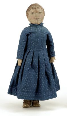 American, ca. 1900, all cloth doll with painted features including wavy brown hair, brown eyes, open closed mouth showing teeth, wearing period blue printed dress with leather baby shoes.