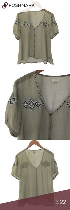 ECOTE BLOUSE ECOTE BLOUSE. AZTEC DETAIL AT NECK AND FRONT. OPEN NECKLINE WITH BUTTON UP FRONT. SHORT SLEEVES. HIGH-LOW NECKLINE. FABRIC: POLYESTER. CONDITION: GENTLY USED/ SIGNS OF WEAR; MINOR FLAWS IN FABRIC. MARKS ON BUTTONS. SIZE XS Ecote Tops Blouses