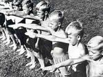 """Hitler's little soldiers, early 1930s. Description: Members of the junior branch of the Hitler Youth - the Jungfolk - on Summer camp, deliver the """"German Greeting"""". Even at this age, Summer camps like this concentrated on the more energetic and physical end of boy scouting, carrying a proto-military edge, as well as indoctrinating young minds with Nazi ideology. Many parents, still suffering from the effects of the post-1929 economic crash, welcomed the HJ's activities as a useful…"""