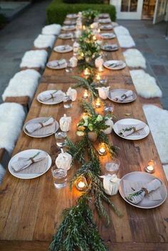 Simple tablesetting, fresh greenery, candles, fur pelts on benches for a warm cozy feeling.