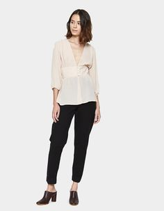 Feminine top from Farrow in Tauple. Semi-sheer fabric. Plunging V-neckline. Three-quarter sleeves with elasticated cuffs. Wide waistband gathered details with front button closure. Unlined. Straight hem.    • Crepe Georgette • 100% polyester • Hand w