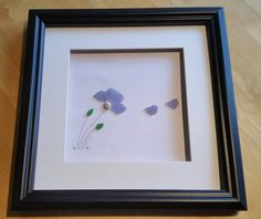 As an extra special offer for Mothers Day Im offering this large frame for a price of just £39.00 One single, beautiful sea glass flower blowing in the wind.  This piece is set inside an impressive 35cm x 35cm glazed box frame that makes a real statement on the wall. It comes in either black or white and you can choose to keep the flower in its natural, delicate shade of blue or have it stained in a colour of your choice.  A perfect gift for an extra special mother - choose her favourite…