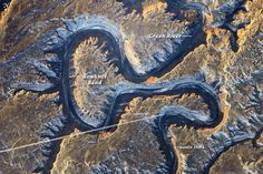 In this photograph taken by an astronaut on the International Space Station, the Green River appears dark because it lies in deep shadow, 300 meters (1,000 feet) below the surrounding landscape. The yellow-tinged cliffs that face the rising sun give a sense of the steep canyon walls. The straight white line across the scene is the contrail from a jet liner that passed over Bowknot Bend. Note that north is to the bottom of the image.
