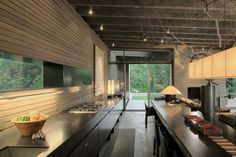 Indoor kitchen station extends outside to create an integration of both the…