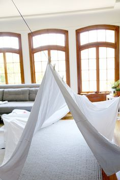 How to build a livingroom fort by stringing a rope across the room and draping a sheet secured by clothes pins over it.  Easy and effective.