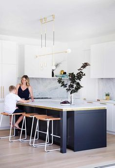 All-white kitchen with navy blue kitchen island topped with marble benchtop in a Hamptons-style home.