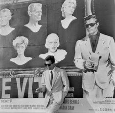 Marcello Mastroianni in front of a poster for his film La dolce vita