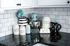 Black, White and Teal Rae Dunn Kitchen Display. SOURCE: lollipopsandlightsabers black and white, modern farmhouse, farmhouse sink, subway tile, black granite, black hardware, white cabinets, whirlpool appliances, teal pantry door, fresh pies, rae dunn.