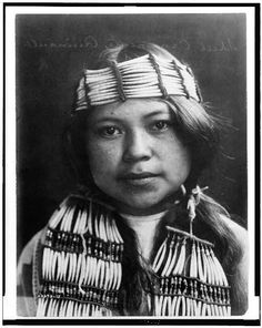 1913 Curtis photo of a young Quinault Indian maiden, head-and-shoulders portrait, facing front, wearing shell ornaments.