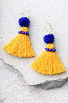 "Add a pop of fun with the Shashi Pom Blue and Yellow Tassel Earrings! Bright yellow threaded tassels dangle beneath royal blue pompoms with matching beads. Earrings measure 3""."