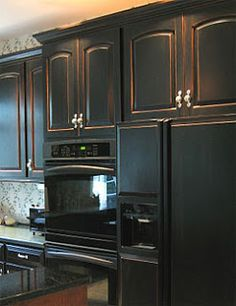 Black cabinets with a distressed hint of warm oak/cherry underneath; all with concrete stained floors & a rich granite countertop & cream walls.
