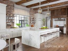 While rustic hand-hewn ceiling beams speak to a casual Texas country style, the custom white cabinets with polished-nickel hardware are clean and contemporary. - Photo: Ryann Ford / Design: Julie Dodson