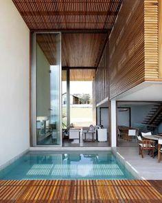 Dois rebaixos - o espelho d'água na frente e a piscina no terraço - fazem a intermediação da sala de estar com o ambiente externo