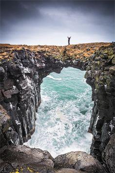 Anastarpi Beach - Hiker on a natural bridge at the Anastarpi coastline, Iceland