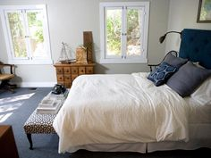 Emily rearranges the bedroom so the bed is facing the window and the beautiful view of the Bronson Canyon. The walls are painted a warm stone color, which keeps the space looking light and airy. Dark charcoal carpet creates contrasts with the walls.