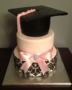 Girly Graduation Cake. Herald the graduate's academic triumph with such a cake for a girl. The topper part of the cake is made from cake cardboard covered in fondant. It has satin ribbon with jewel detail for pretty decoration.