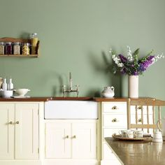 grey/green wall, white cabinets, brass handles, wood counter top