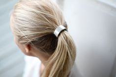 "Hair Cuff - Silver | Take a classic pony from plain jane to chic with this hair cuff, as seen on the runway! Gold spring hinge cuff covers attached hair tie.  .7"" barrel.  Available in gold and silver."