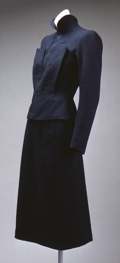 Although sinuous curves ruled the evening wear silhouette in the 1930s, the strong shoulder was a dominant element as well, especially in the crisp suits of Elsa Schiaparelli.