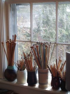 Knitting needles (and some crochet hooks) displayed in various stoneware vessels