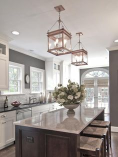 White cabinets, grey walls, neutral backslash, dark island--design by Carolina Design Associates