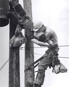 """A 1967 award-winning photo called """"The Kiss of Life"""" by Rocco Morabito. Randall Champion brushed a high voltage line during maintenance and over 4000 volts surged through his body, stopping his heart. Fellow lineman J. D. Thompson quickly reached him and performed mouth-to-mouth resuscitation until he felt a pulse. He unbuckled Champion's harness and descended with him on his shoulder. On the ground Thompson and another worker administered CPR and ultimately helped parademics to save…"""