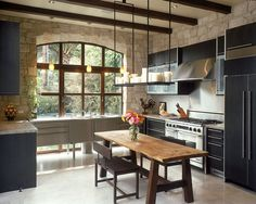 Modern Mediterranean kitchen with custom arched window and stone walls [Design: DuCharme Architecture]