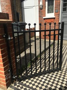West London - edwardian house front garden. Pretty wrought iron gate with red brick wall and iron railings and capping.