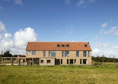 House in England designed by Lucy Marston to reference old English farmhouses. It features red brickwork, a steep gable and a corner chimney.
