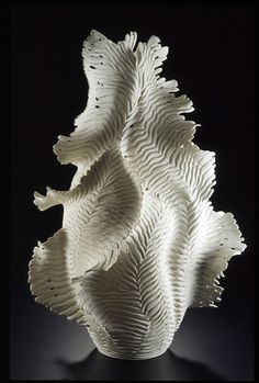 """""""Ocean Lace"""" by Debra Steidel - clay """"This piece was about 26"""" tall when it went into the kiln, about an inch shy of the top. It was thrown in 2 pieces, altered and then coils of clay added to the sides and pulled out into wings. When it was leather hard, I carved the groves and edges and pierced the holes. It was fired to cone 10 with no glaze."""""""