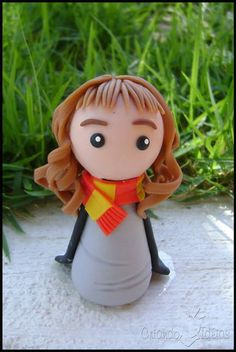 """Hermione Granger, personagem da saga literária """"Harry Potter"""", da escritora britânica J.K. Rowling. Personagem modelada em estilo chibi (infantil simplificado), ideal para lembrancinhas =) Ela pode vir acompanhada ou não de base, à escolha do cliente (conforme fotos ao lado) OBS: A peça tem 10cm. Se o cliente desejar que seja feito para lembrancinhas, pode-se diminuir o tamanho e o preço. Consulte! Material utilizado: porcelana fria (biscuit). ----------- Novidade! ----------- Tenho também …"""