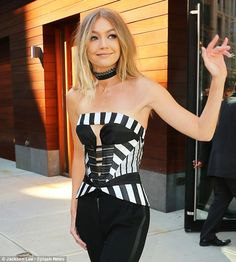 Turning heads: The 21-year-old beauty donned a striped corset with cut-out design along with black Adam Lippes trousers which flattered her slender figure