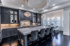 The Goal: A different type of kitchen. We balanced the dark gray cabinets and dark hardwood with a quartzite countertop and white backsplash. The mirrored cabinets and crystal pendants added just the right glamour to an otherwise functional and clean kitchen.