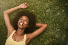 Mulher deitada na grama sorrindo